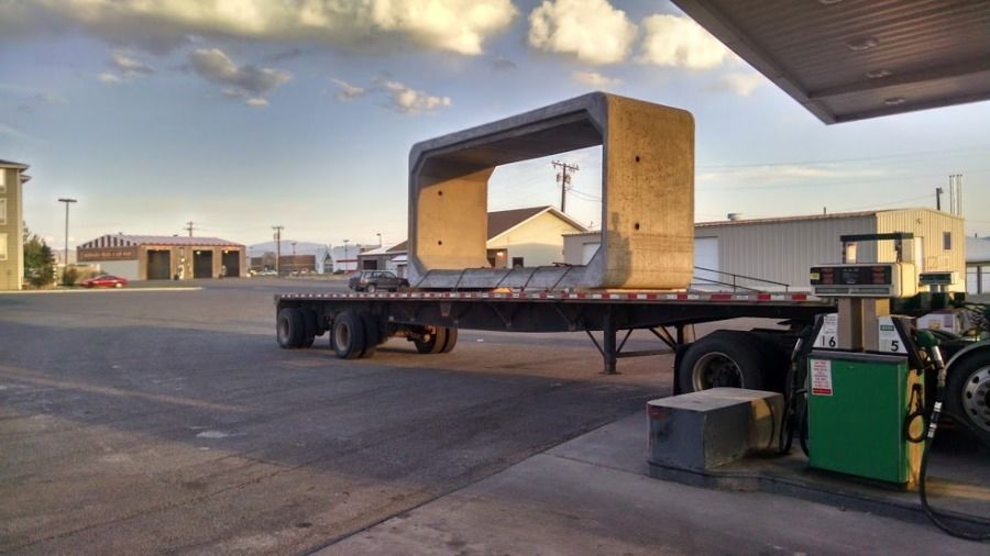 large cement box culvert loaded and chained on a flatbed trailer
