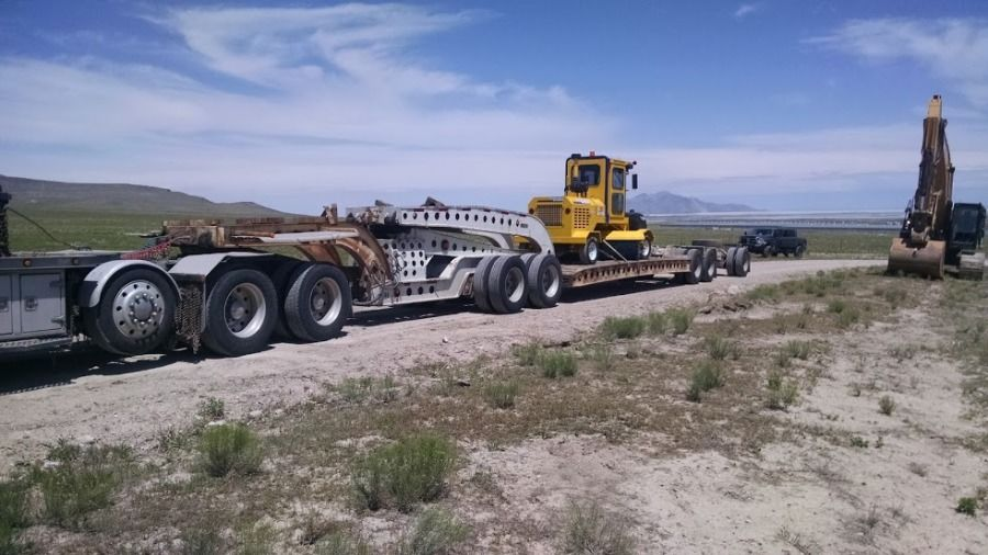 construction equipment yellow road sweeper loaded on flatbed trailer