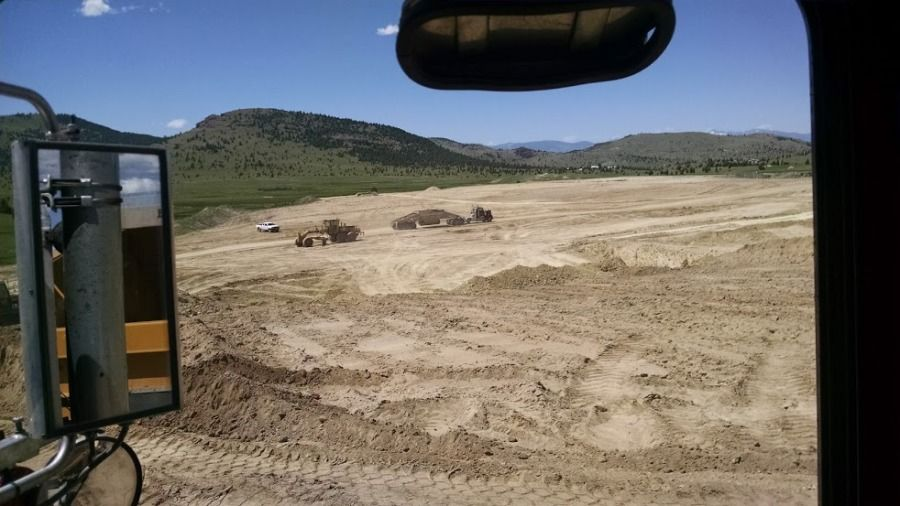 truck driver looking out window picking up at dirt mine