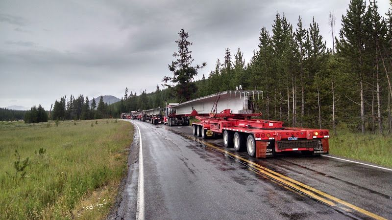 flatbed trailers with dollies carrying giant cement bridge beams