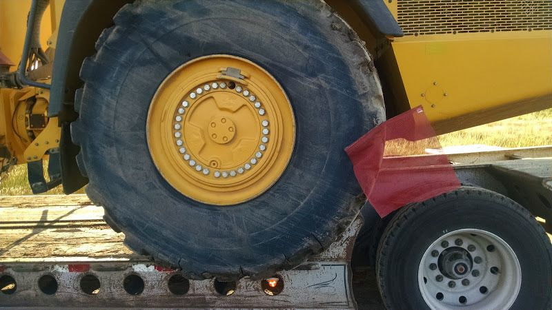 nail in tire used to secure flag on oversized piece of construction equipment loaded on flatbed trailer