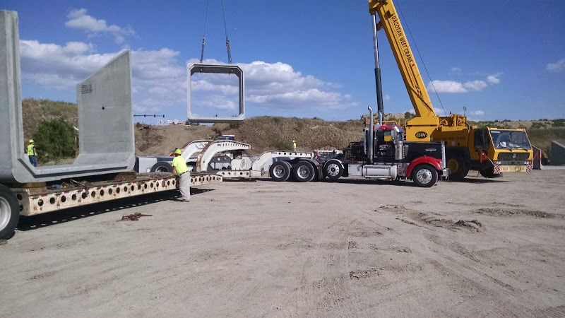 oversize flatbed being loaded with cement boxes by a crane