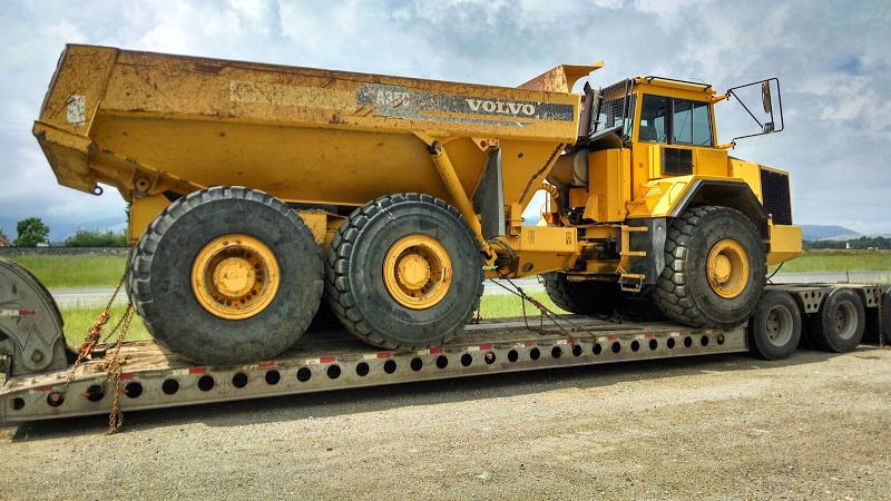 flatbed trailer loaded with yellow oversized Volvo dump truck
