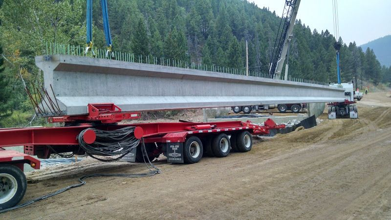 oversize flatbed trailer loaded with cement bridge beams being unloaded by a crane at construction site