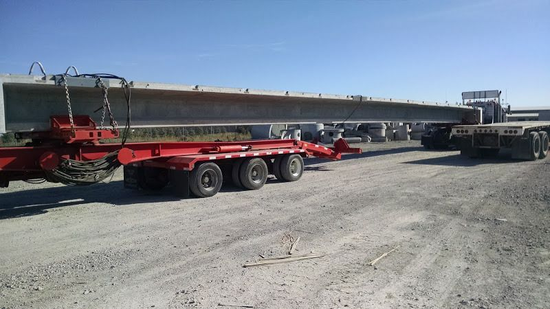 Over-sized cement bridge beam secured to flatbed dolly trailer