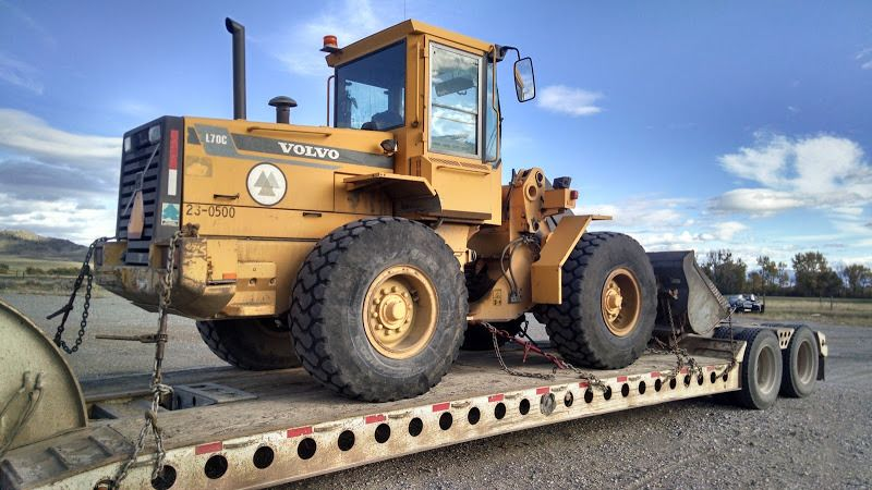 small Volvo loader chained to a flatbed trailer