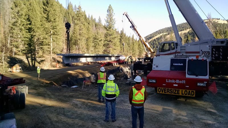 crane unloading large cement bridge beams from flatbed trailer dolly