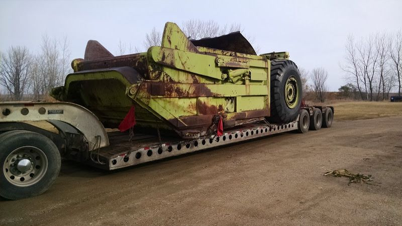 large yellow piece of construction equipment loaded on flatbed trailer