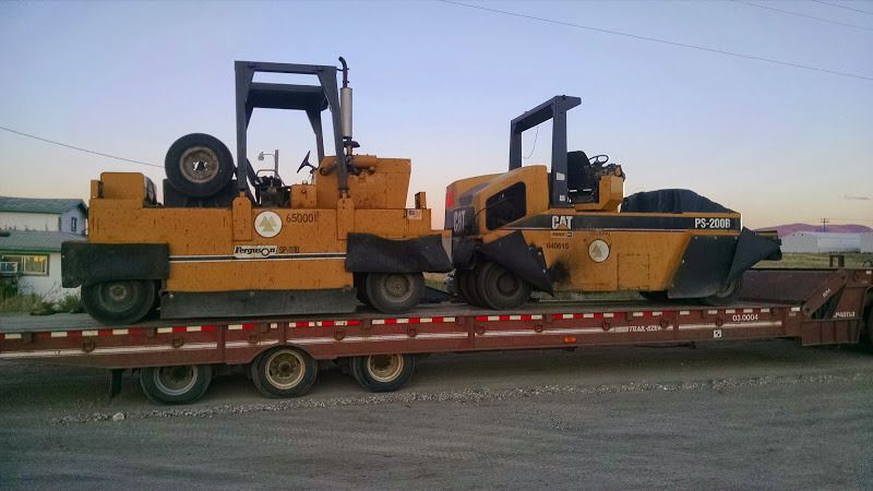 small yellow CAT pavers loaded on trailer