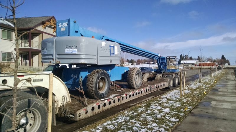 blue genie boom bucket-lift chained to flatbed trailer