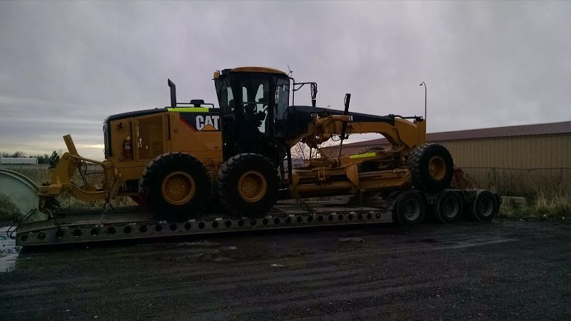 large yellow CAT grader loaded and chained on flatbed trailer