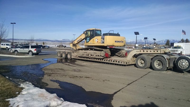 270 Komatsu loader secured to a flatbed trailer