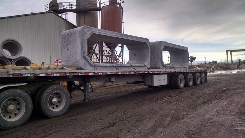 heavy 50,000 lb cement boxes bridge columns chained on flatbed trailer
