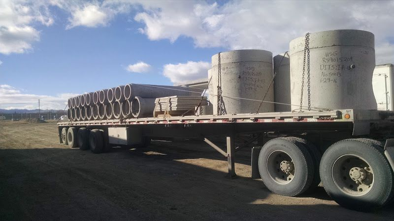 flatbed trailer loaded with cement pipe and manholes strapped chained cabled