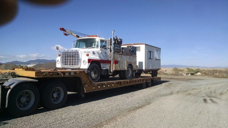 flatbed trailer carrying phone utility truck