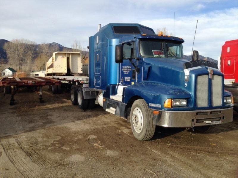 used Kenworth blue semi truck with flatbed trailer