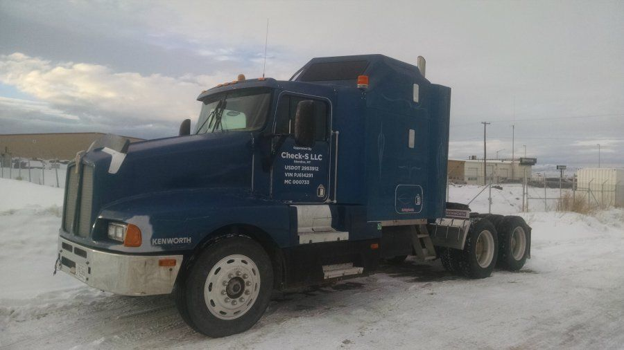 old blue long-nose semi truck outside in the snow